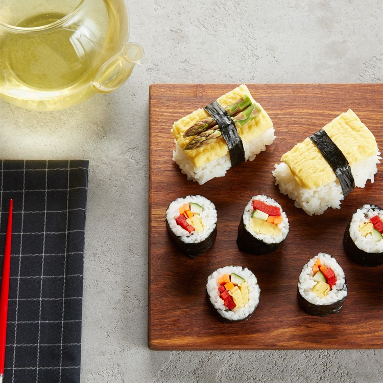 sushi on a serving board with chopsticks and tea