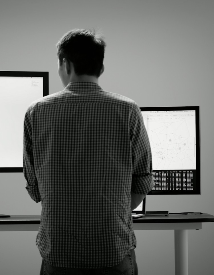 A person at a standing desk looking at two computer monitors