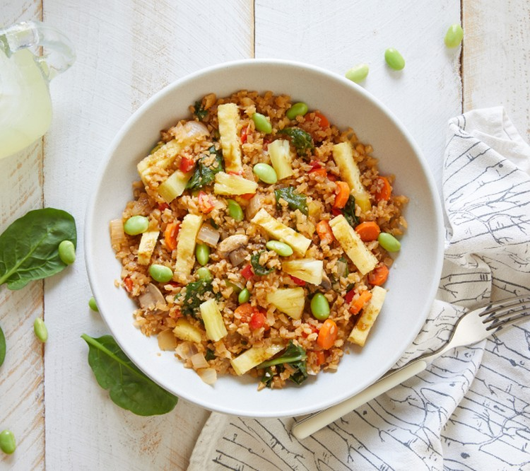 cauliflower fried rice bowl with a fork and napkin